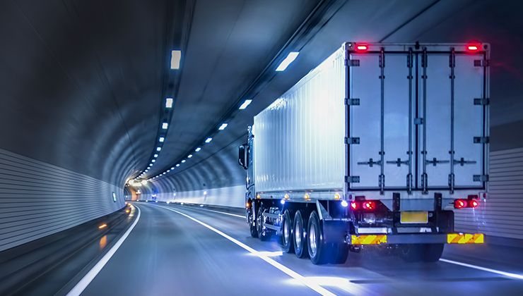 A container truck travelling through an underground tunnel in an advanced manufacturing hub